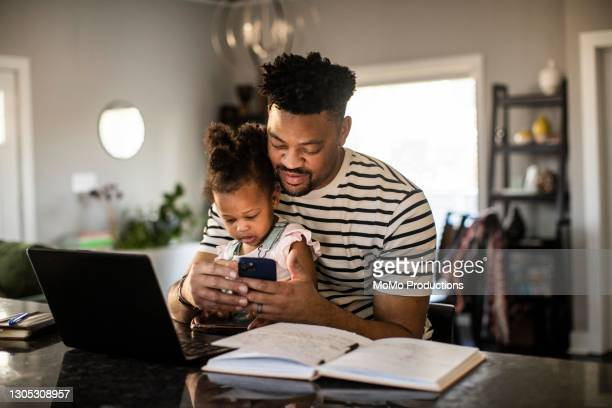 father working from home while holding toddler - lifestyle stock pictures, royalty-free photos & images