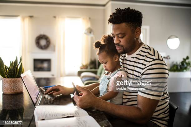 father working from home while holding toddler - african ethnicity stock pictures, royalty-free photos & images
