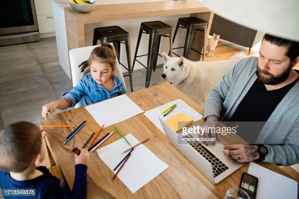 father working from home with young children in quarantine isolation covid-19 - confined space stock pictures, royalty-free photos & images