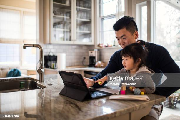 Father working in kitchen with daughter