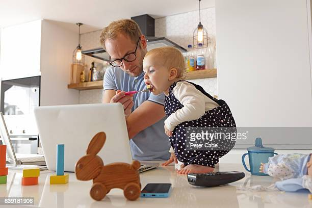 father working on laptop whilst looking after toddler - genderblend stockfoto's en -beelden