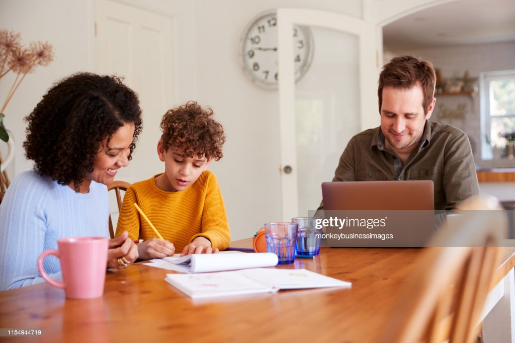 Father Works On Laptop As Mother Helps Son With Homework On Kitchen Table : Stock Photo