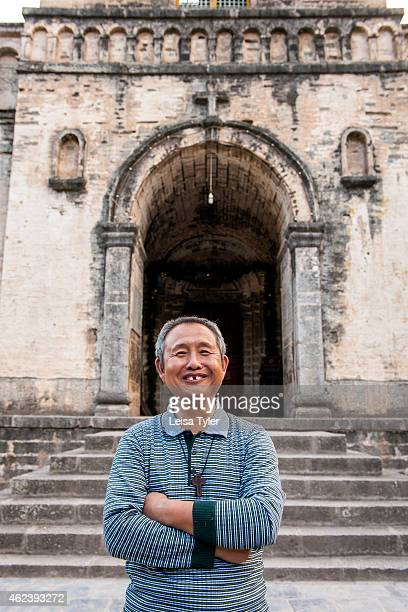 Father Yeoh in front of Cizhong church a stone and stucco church built in 1910 by early French missionaries in Cizhong a small village that sits on...