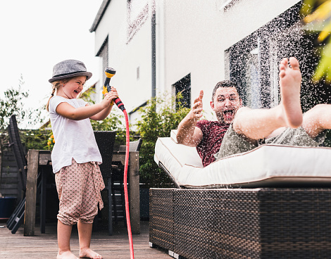Fathercand daughter in the garden, daughter splashing water with hose - gettyimageskorea