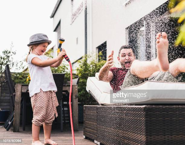 fathercand daughter in the garden, daughter splashing water with hose - nass stock-fotos und bilder
