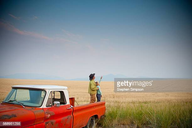 Father/daughter standing back of old pickup truck