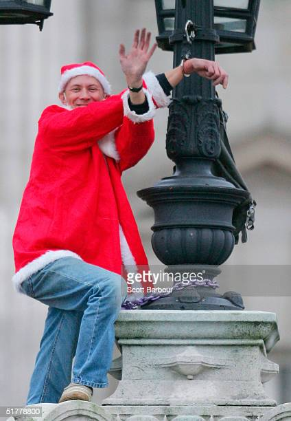 Fathers 4 Justice protestor, David Pyke dressed as Father Christmas waves after he chained himself to the top of the gates of Buckingham Palace on...