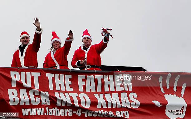 Fathers 4 Justice protestors wave at a train as it passes under a signalling gantry December 16, 2004 in London, England. Fathers 4 Justice is a...