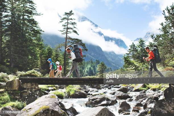 fathers and children hiking together in mountains - backpacker stock pictures, royalty-free photos & images