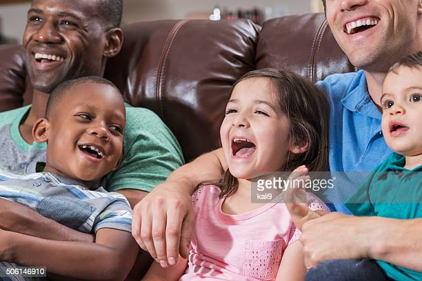 Fathers and children sitting on couch watching TV
