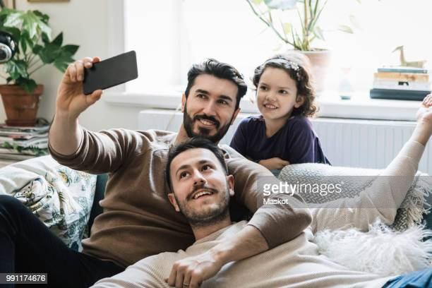 Fathers and daughter taking selfie through mobile phone in living room at home