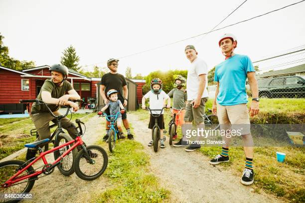 Fathers and sons hanging out in backyard after riding BMX bikes on summer evening
