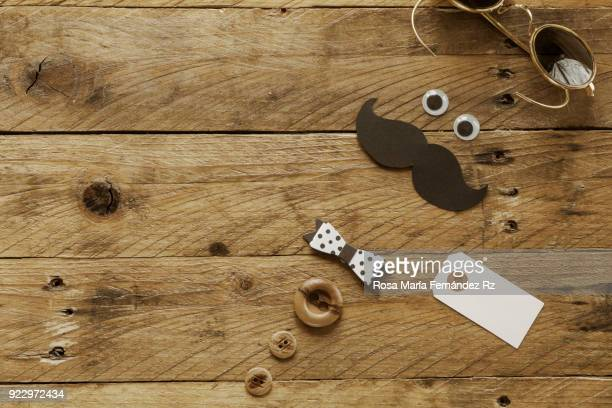 Father's day concept. A pair of sunglasses, funny eyes, moustache, paper bow tie,  blank tag and three buttons depicting a man face on a rusting wooden. Directly above and copy space.