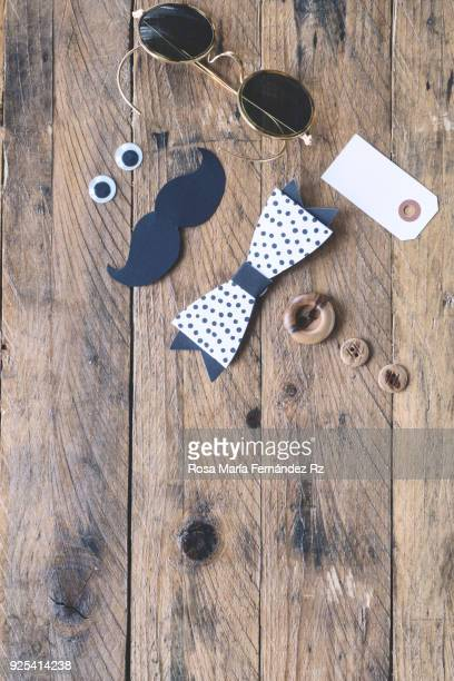 Father's day concept. A pair of sunglasses, funny eyes, moustache, paper bow tie, blank greeting card and three buttons depicting a man face on a rusting wooden. Directly above and copy space.