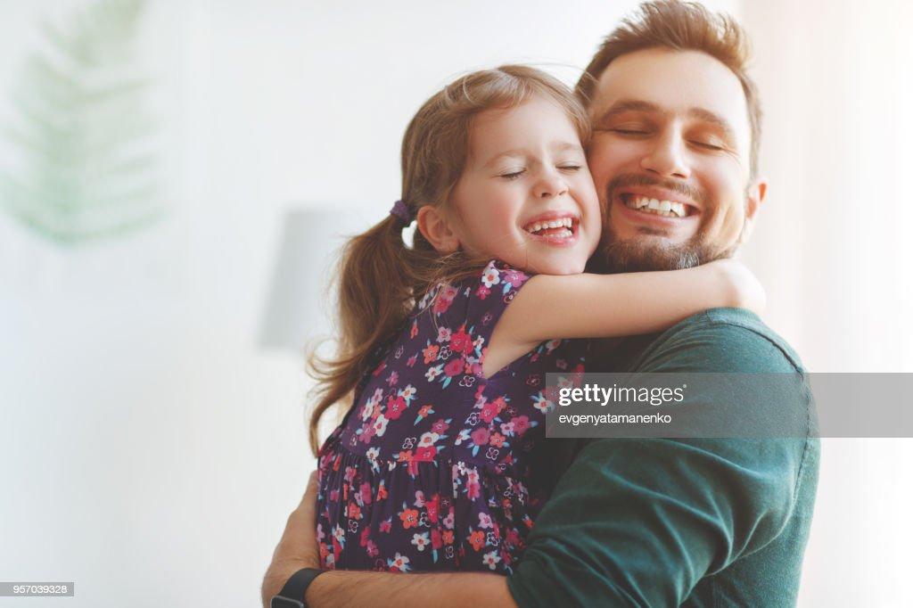 Father's day. Happy family daughter hugs his dad : Stock Photo