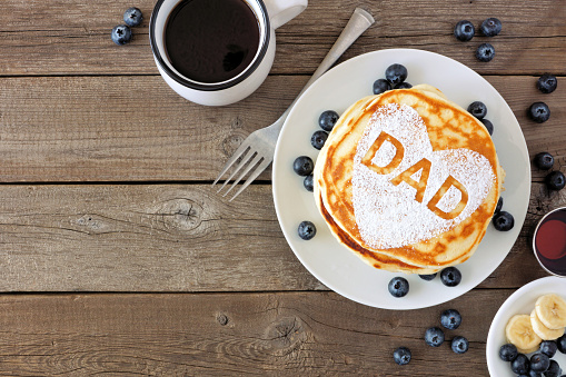 Fathers Day pancake breakfast with heart shape and DAD letters, above view corner border on rustic wood 1145934712