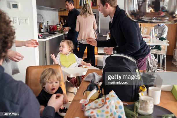 fathers feeding toddlers before big family dinner, lots of action. - affollato foto e immagini stock