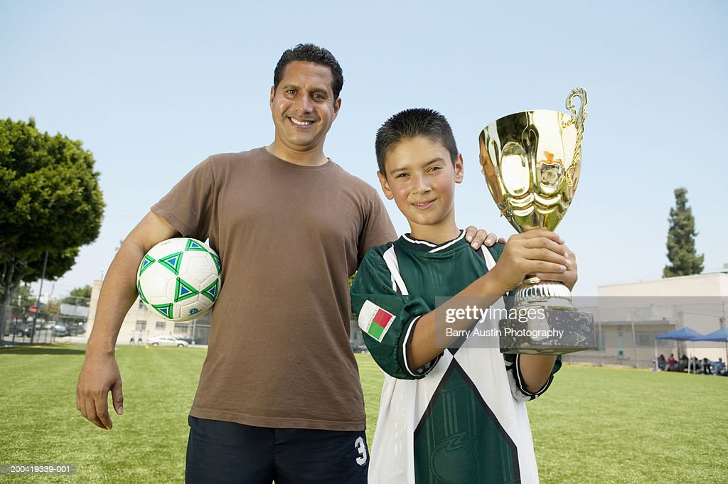 Father's hand on son's (7-9) shoulder, boy holding trophy, portrait : Stock Photo