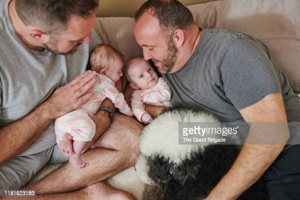 fathers lying in bed with baby girls and dog - lgbtq  and female domestic life fotografías e imágenes de stock