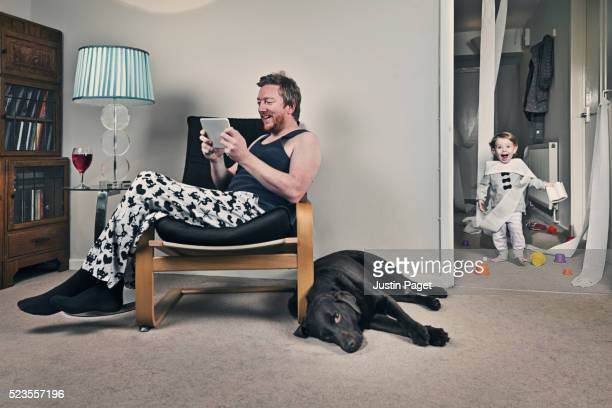 fathers on tablet whilst baby causes chaos - funny toilet paper stock pictures, royalty-free photos & images