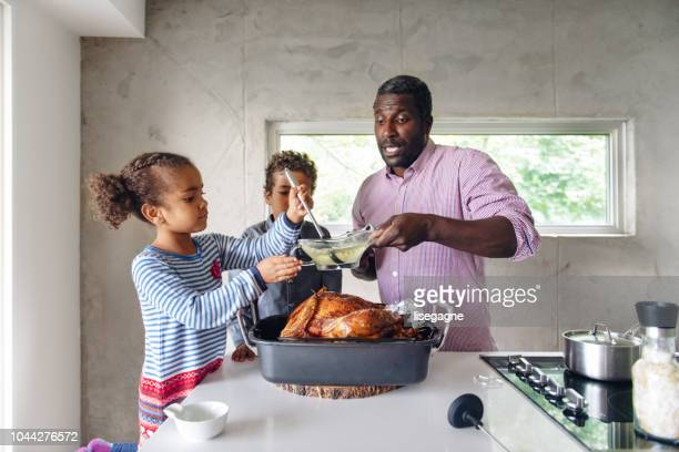 fathers preparing thanksgiving turkey - canadian thanksgiving stock pictures, royalty-free photos & images