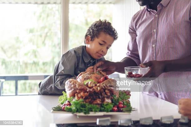 fathers preparing thanksgiving turkey - african american family dinner stock photos and pictures