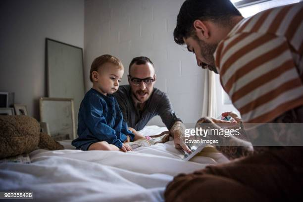 fathers showing tablet computer to daughter while sitting on bed at home - gay person stock pictures, royalty-free photos & images