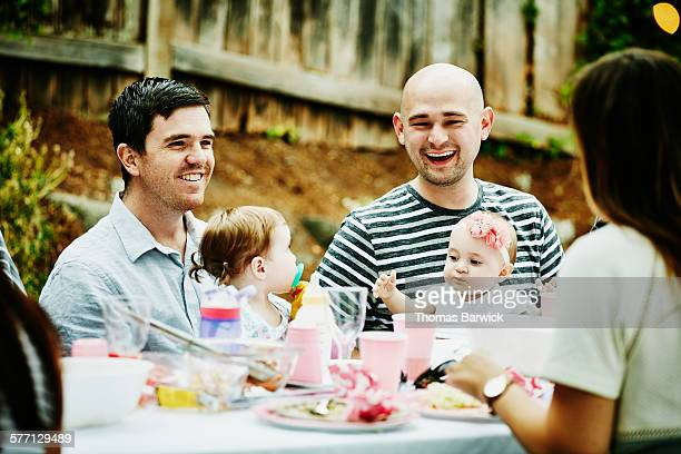 Fathers sitting at table with infant daughters