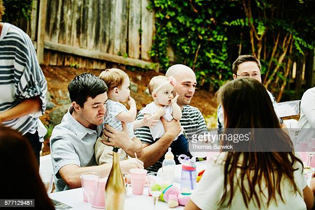Fathers trying to eat while holding daughters
