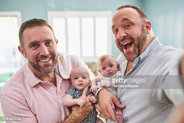 fathers tsking selfie at home with baby girls - lgbtq  and female domestic life fotografías e imágenes de stock