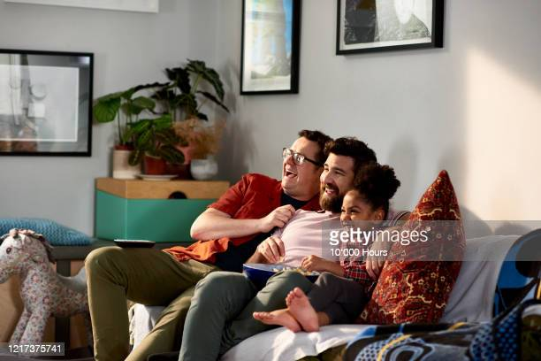 fathers with adopted daughter laughing together on sofa - couple relationship stock pictures, royalty-free photos & images