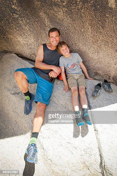 Father/son hikers rest/relax in the shade
