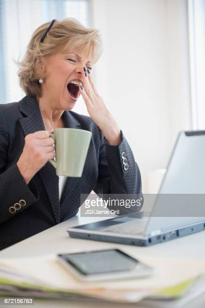 Fatigued Caucasian businesswoman drinking coffee and yawning