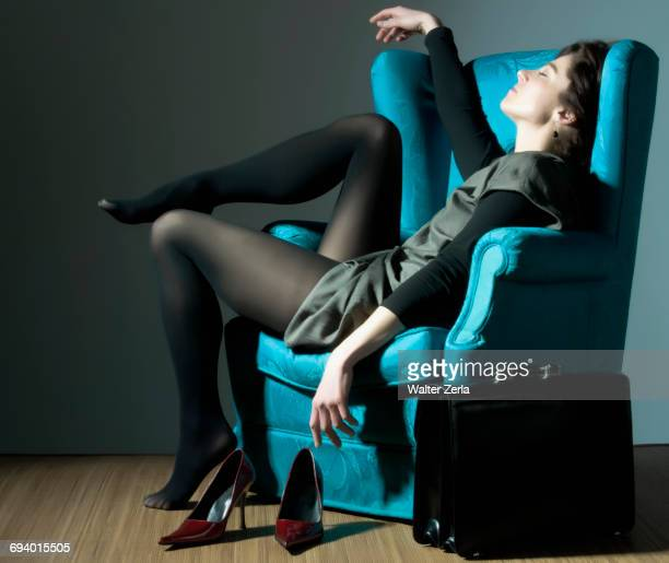 fatigued caucasian businesswoman unwinding in blue armchair - scarpa rossa foto e immagini stock