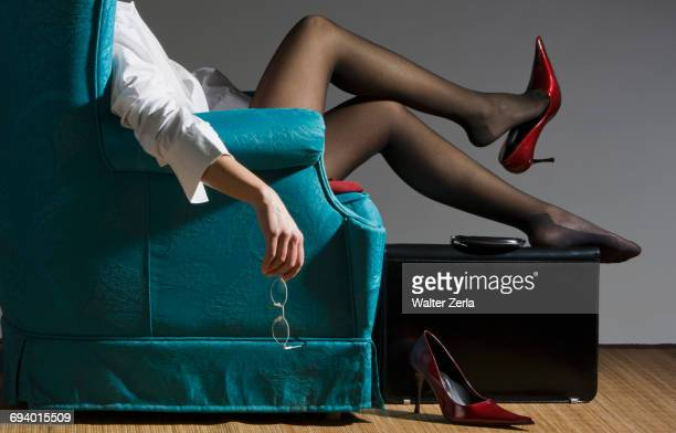 Fatigued Caucasian businesswoman unwinding in blue armchair