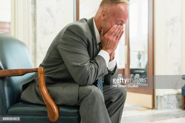 fatigued caucasian politician sitting in armchair rubbing eyes - tensed idaho stock photos and pictures
