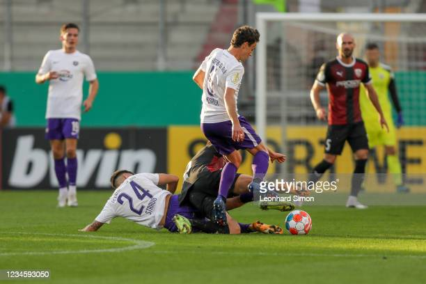 Fatih Kaya of FC Ingolstadt 04 and John-Patrick Strauß and Clemens Fandrich of Erzgebirge Aue in action during the DFB Cup first round match between...