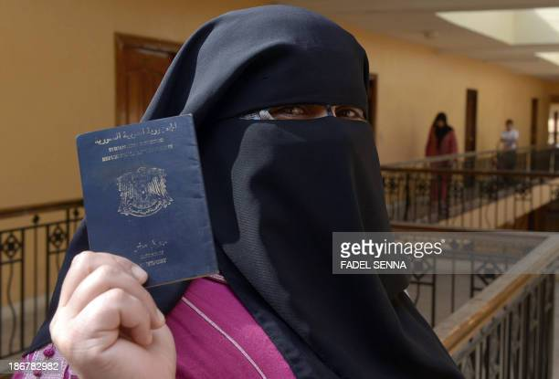 Fatima a 45yearold Syrian refugee from the central city of Homs flashes her passport in Tangier Morocco on October 28 2013 Fatima arrived in Morocco...