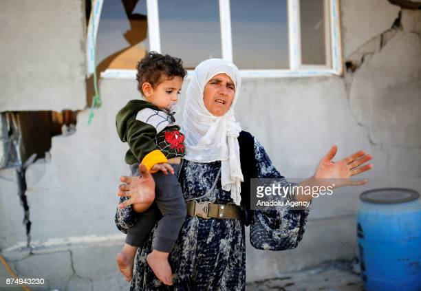 Fatima Mohamed Karim holds a baby in front of a damaged house during an interview at the quakehit area in Karavuta village of Derbendihan district in...