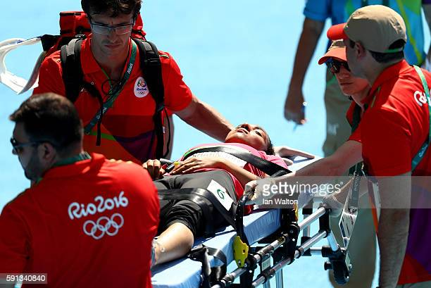 Fatma El Sharnouby of Egypt is taken off the field of play by medical staff during the Women's 800m Round 1 heats on Day 12 of the Rio 2016 Olympic...