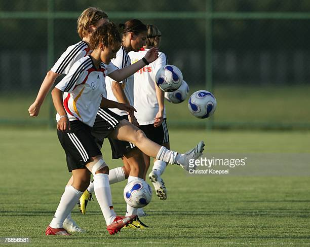 Fatmire Bajramaj, Melanie Behringer and Linda Bresonik juggle with the ball during the Women's German National Team training session on the training...