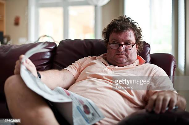 fatso reading the paper - chubby men stock photos and pictures