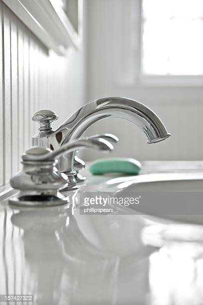 Faucet in  white bathroom with a bar of soap.