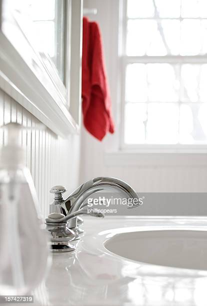 Faucet in  white bathroom with a red towel.