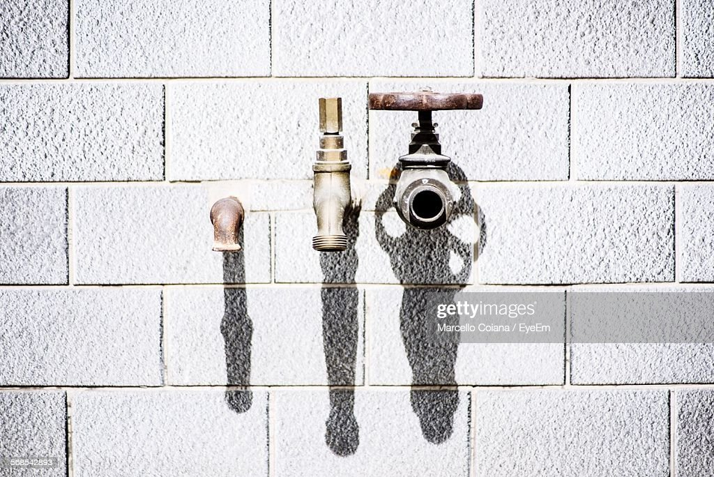 Faucets On Brick Wall : Stock Photo