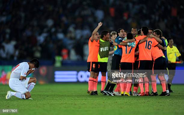 Faustino Rojo of Estudiantes kneels dejectedly while Barcelona players celebrate their victory at the end of the Club World Cup Final match between...