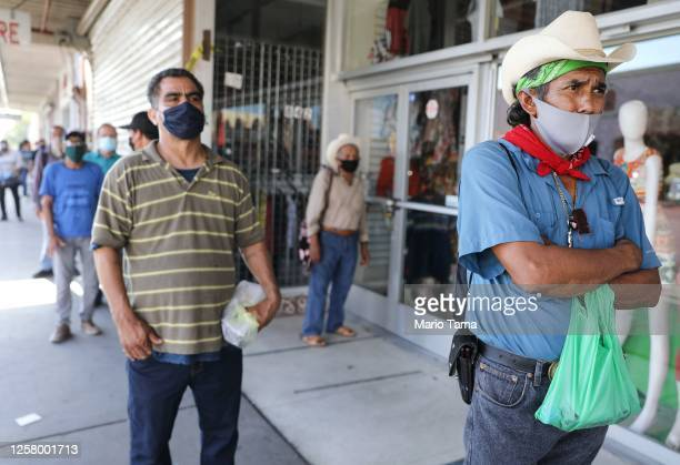 Faustino , who is currently unemployed, waits in a socially distanced line to enter a bookkeeping shop near the U.S.-Mexico border in Imperial...