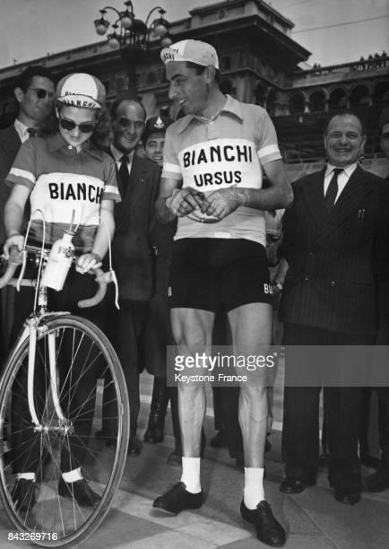 Fausto Coppi avec une jeune admiratrice regardant son vélo avant le départ du Tour à Milan Italie le 24 mai 1950