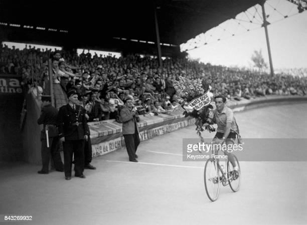 Fausto Coppi vainqueur du Tour de France un bouquet de fleurs dans les mains effectue sur son vélo le tour d'honneur sur la piste du Parc des Princes...