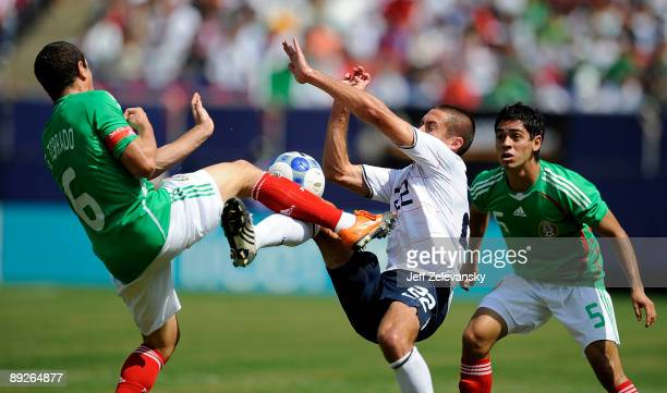 Fausto Pinto watches as teammate Gerardo Torrado of Mexico collides with Davy Arnaud of the United States in the CONCACAF Gold Cup Championship match...